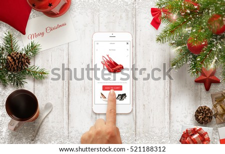 woman buy shoes online with mobile phone during christmas time table with christmas decorations