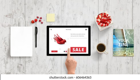Woman buy shoes with tablet on online market web site. Shopping bag, gift box, magazine, coffee, note, pencil, strawberries and raspberries beside. Top view of white wooden desk.