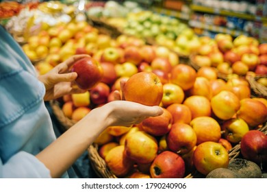 Woman buying apples in the store close up