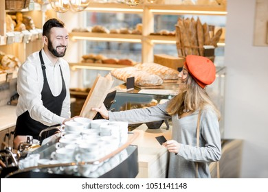 Woman buying baguette in the small and cozy coffee house with bakery products