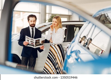 Woman buying the car. Lady in a car salon. Manager with a client