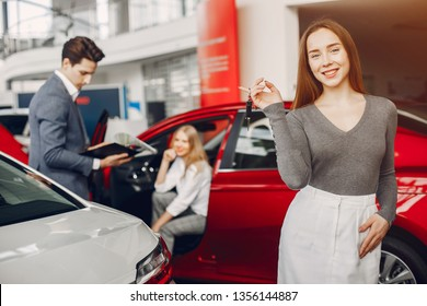 Woman buying the car. Lady in a car salon. Manager with a clients
