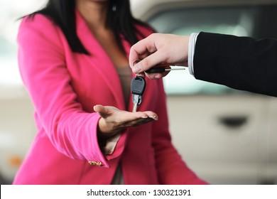 Woman buying a car and salesman handling keys