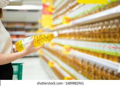 Woman buying cooking oil in supermarket