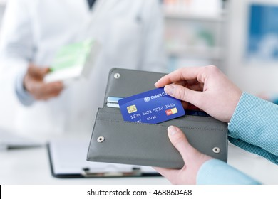 Woman buying drugs and medical products in the pharmacy, she is taking the credit card from the wallet