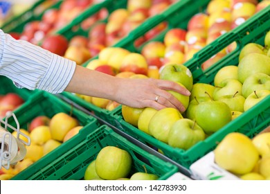 Woman buying a fresh green apple in a supermarket reaching across to remove one from a bin in the display