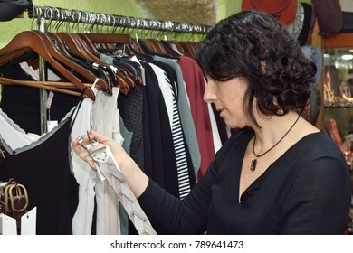 woman buying a hat in clothing market
