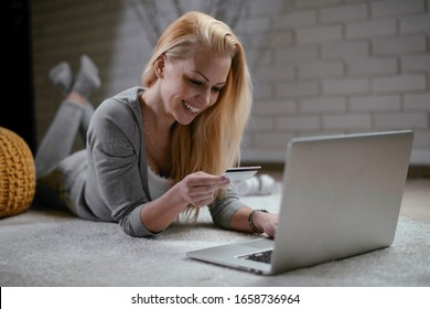 Woman buying online. Beautiful woman lying on floor with laptop and credit card.