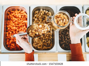 Woman buying pasta in plastic free grocery store. Bulk foods in zero waste shop. Customer doing shopping without plastic packaging. Concept of minimalist lifestyle, eco friendly living, less waste