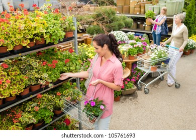 Woman buying potted flower in garden center shopping basket greenhouse