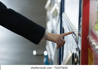 Woman buying with a vending machine