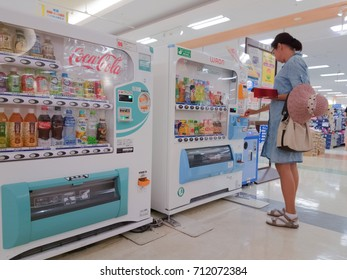 woman buys drinks in the automatic machine of Yonago, Japan, 08.08.2017