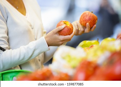 Woman buys fruits and vegetables at a market, apple