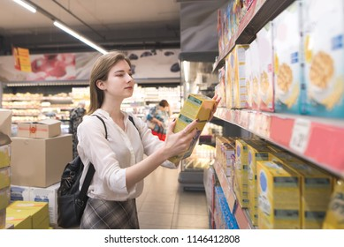 Woman buys quick breakfasts at a supermarket. Girl isa in the store with a box of flakes and hands. Woman chooses the products in the supermarket.