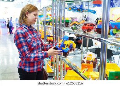 Woman buys a toy car tractor in a children's store