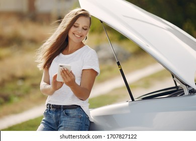 Woman by the car. Lady in a white t-shirt. Woman with mobile phone.