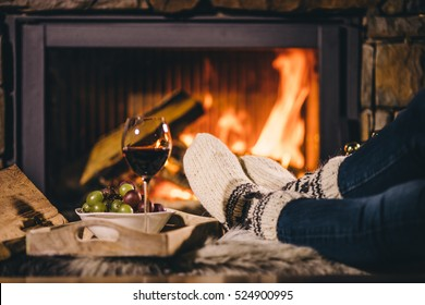 Woman by the fireplace. Woman in woollen socks taking a glass of red wine relaxing by the cozy fireplace. Snug winter evening.
