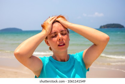 Woman by seaside with sunstroke. Health problem on vacation. Medicine on vacation. Dangerous sun. Beach day. Sunstroke on hot beach. Girl under sun. Unhealthy girl on beach by sea. Holiday health care