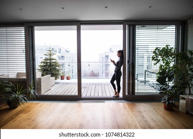 Woman by the window with smartphone, text messaging.
