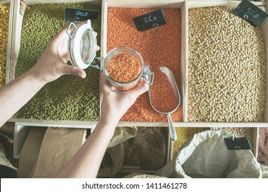woman is bying products in zero waste shop with glass jars, cotton bags with out plastic packages