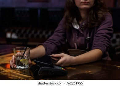 woman in cafe, coffee shop or bar making mobile payment.