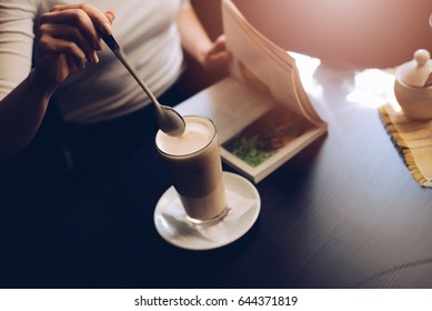 Woman cafe customer mixing caffe latte with spoon and reading a book