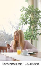 Woman in cafe drinking coffee and using her mobile phone.