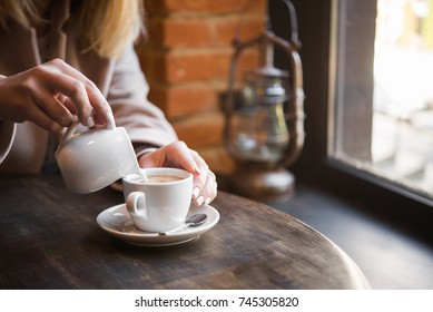 woman in a cafe pours milk cream into coffee cup. businesswoman  lifestyle background