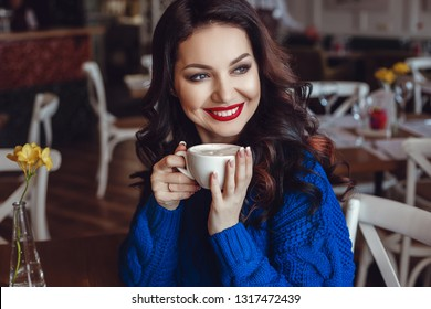 the woman in the cafe sits at a table, drinks coffee and looks at window. A woman with red lipstick and in a blue sweater is waiting for a meeting, talking on the phone and smiling a lot.