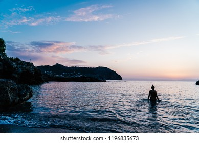 A woman at Cala Rotja is looking at the sky and the sun really early in the morning. Sunrise in Majorca, Spain.. Lifestyle.