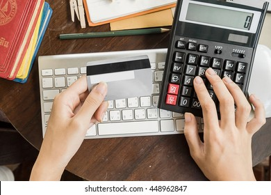 woman calculate how much cost or spending have with credit cards. Low light, selective focus on hand, can be used for e-commerce, business, technology and internet concept, Vintage tone