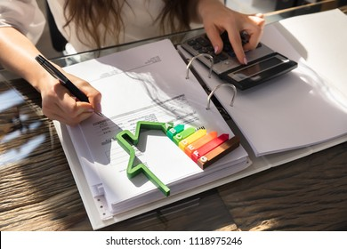 Woman Calculating Invoice With Energy Efficient Chart And House Silhouette In Office