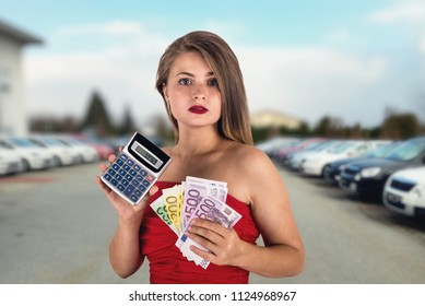 Woman with calculator and euro on car show background