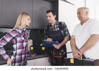 The woman called two plumbers to repair the kitchen sink. The men brought with them all the necessary tools in the black tool boxes. A woman talks about her problem.