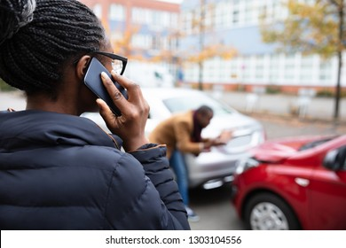 Woman Calling For Assistance In Front Of Man Inspecting Damaged Car On Road