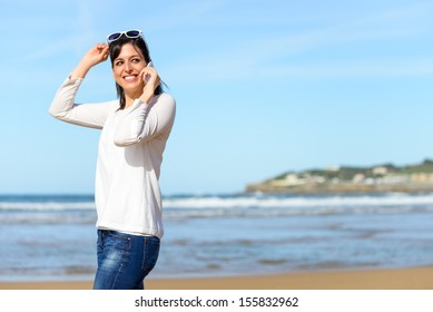 Woman calling by cell phone and walking on beach. Brunette woman on travel vacation mobile conversation smiling.
