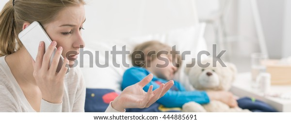 Woman calling a doctor, in the background ill boy lying in bed