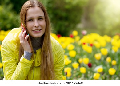 Woman calling on the mobile phone in a green field with yellow flowers