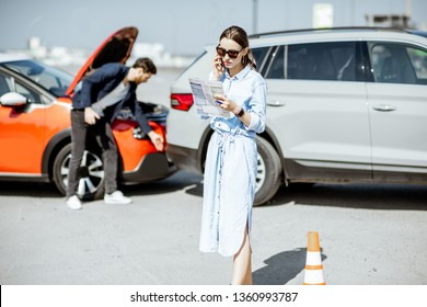 Woman calling road assistance or insurance company standing on the road after the car collision, man checking the damage