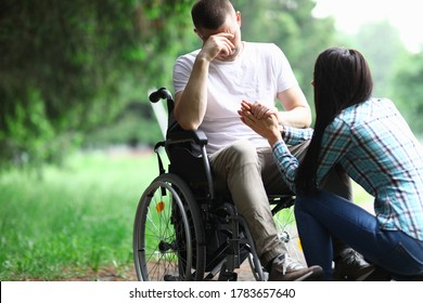 Frauen beruhigen den Mann im Rollstuhl. Behinderte sitzen im Rollstuhl, bedecken sein Gesicht mit der Hand und werden verärgert. Staatliche Unterstützung für Kinder, die Kinder mit Behinderungen aufziehen. Leistungen, Rechte und