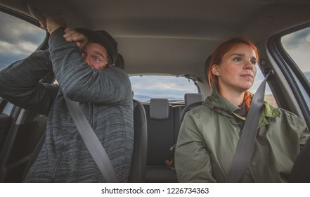A woman is calmly driving a car and a man in the next seat is scared as hell. Totally scared co-driver because of reckless careless driving by a woman.