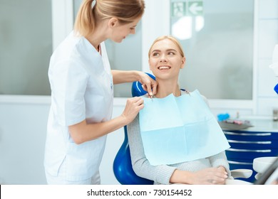 The woman came to see the dentist. She sits in the dental chair. The dentist bent over her.