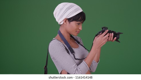 Woman with camera reviewing picture she just took on green screen