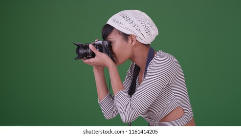 Woman with camera taking photo on green screen