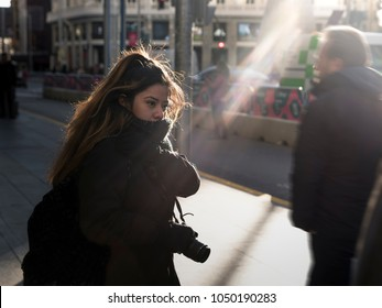 Woman with camera walking in the city street in a cold winter day illuminated by sunbeams