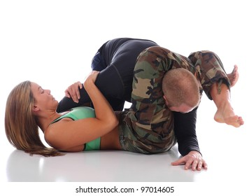 Woman in camouflage practicing Brazilian Jiu-Jitsu with an opponent