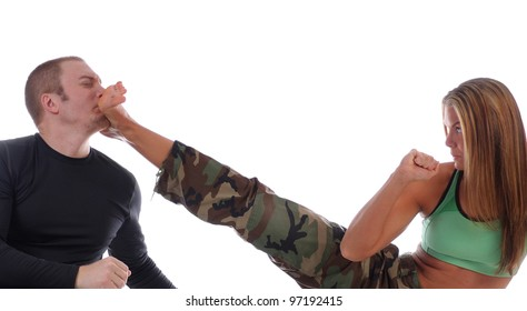 Woman in camouflage practicing kickboxing against an opponent