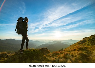 The woman with a camping backpack standing on the rock with a picturesque sunset