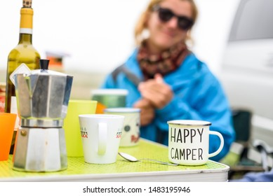 Woman camping travelling with breakfast mug and happy camper text. Woman drinking coffee or tea from special mug when camping or travelling with motor home or campervan. Vanlife camping concept.