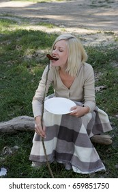 Woman at campsite eating a hotdog